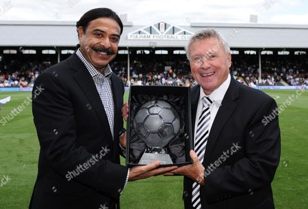 Fulham Chairman Shahid Khan presents David Hamilton with an engraved glass football as he bows out after 18 years as the club's PA Announcer.
