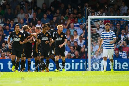 Charlie Austin of QPR walks past a group of players celebrating the goal of James Chester of Hull City, 0-1