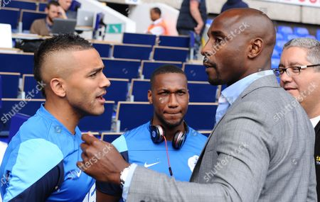 Danny Simpson and Junior Hoilett of QPR chat to former player Jason Roberts before kick off