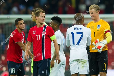 Morten Gamst Pedersen of Norway looks on as England Goalkeeper Joe Hart shakes the hand of Fabian Delph