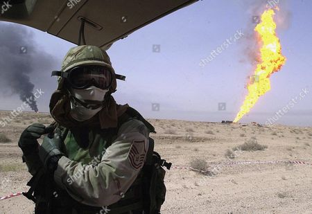 Master Sgt Joe Cross roping off a safe area far from an uncontrolled natural gas fire in the Rumaylah oil fields. Cross and other explosives ordnance disposal airmen are disarming any unexploded ordnance, land mines or booby traps to help firefighters safely tackle the blaze - 23 Mar