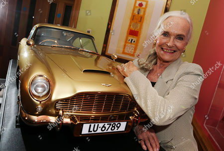 Shirley Eaton with model of gold Aston Martin DB5 sportscar