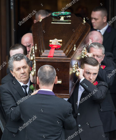 Pallbearers carry the coffin out of the cathedral