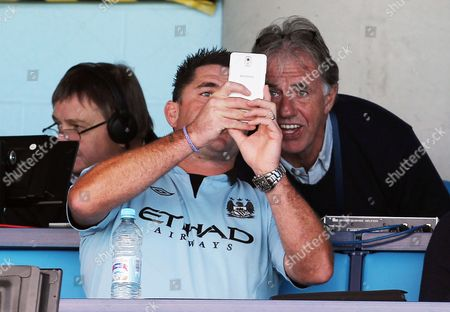 A Manchester City fan gets a selfie with Mark Lawrenson before the game