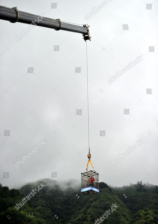 Editorial picture of Chained escapologist escapes from cage dangling above lake, Zhangjiajie city, Hunan province, China - 19 Sep 2014