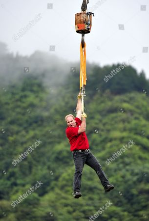 Stock Photo of Canadian escapologist Dean Gunnarson hangs from a crane after escaping the cage