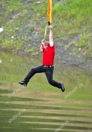 Stock Image of Canadian escapologist Dean Gunnarson hangs from a crane after escaping the cage