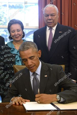 United States President Barack Obama, with America's Promise Alliance Founding Chairman and former US Secretary of State General Colin Powell (R) and current Board Chair Alma Powell (L), signs the America's Promise Summit Declaration