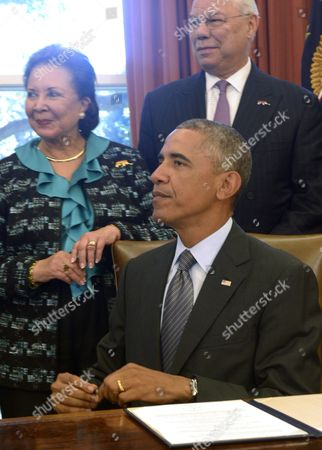 United States President Barack Obama, with America's Promise Alliance Founding Chairman and former US Secretary of State General Colin Powell (R) and current Board Chair Alma Powell (L), listens to a question from the news media after signing the America's Promise Summit Declaration