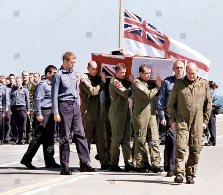 The coffins of Lieutenants Tony King, Phil Green and James Williams starting their final journey back to Britain from the flight deck in front of the shipÕs company