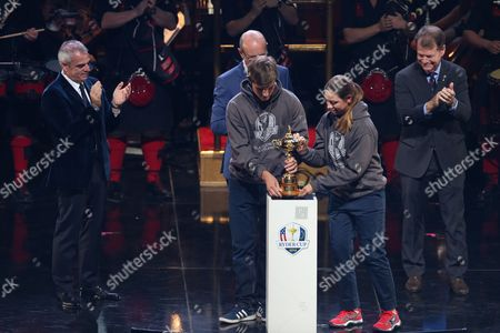 The Ryder Cup is brought on stage by Bradley Neil and Kristen Gillman while watched by Paul McGinley, Europe team captain (far left), Fred MacAulay and Tom Watson, US team captain (far right).