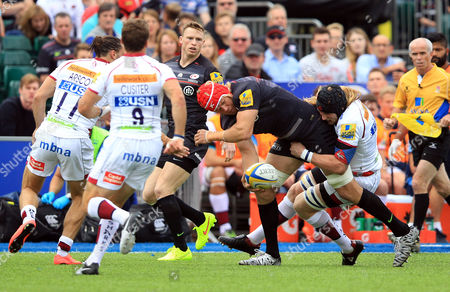 Saracens' Mouritz Botha sneaks a pass away as he's tackled by Sale's Magnus Lund