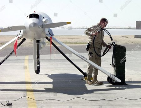 Staff Sergeant James Barr connects a power cart to an RQ-1 Predator to start the engine for a mission with the unmanned vehicle