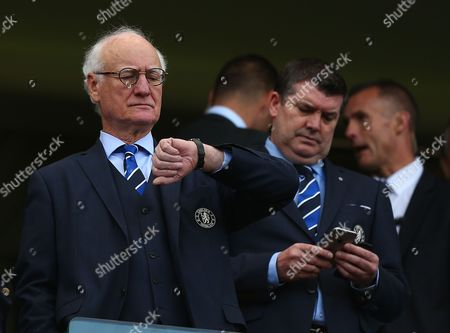 Chelsea chairman Bruce Buck checks his watch as chief executive Ron Gourlay checks his phone as the match is delayed by 15 minutes due to 'an incident'