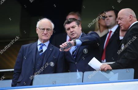 "Chelsea Chief Executive Ron Gourlay looks at his watch alongside Chairman Bruce Buck as kick off is delayed due to an ""incident"""