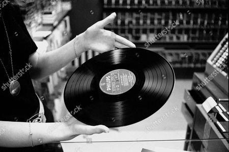 A WOMAN CHECKS A ROGER WHITTAKER RECORD