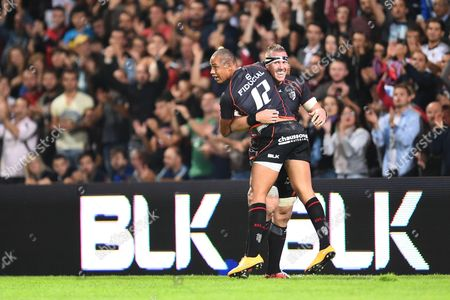 Toulouse's players Gael Fickou and Imanol Harinordoquy celebrate Kickou's try