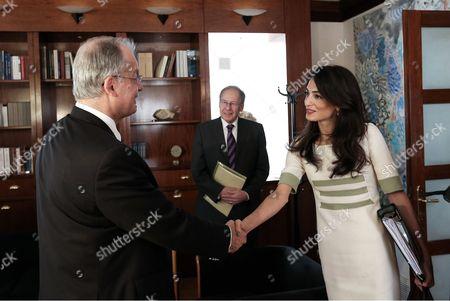 Amal Clooney (R) greets Greek Culture Minister Kostas Tasoulas (L)