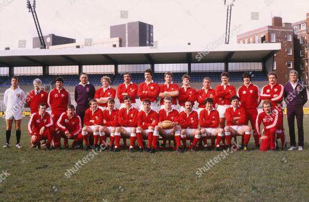 Rugby Union - 1983 Five Nations Championship - Wales v Ireland at Cardiff Arms Park - Wales team. Back (l-r): Tony Trigg (referee - RFU), John Bevan (Welsh coach), Gareth Davies (sub), Alan Welsby (touch-judge - RFU), Graham Price, Jeff Squire, Bob Norster, John Perkins, Robert Ackerman, Staff Jones, David Pickering, Mark Douglas (sub), Ian Stephens (sub), Roger Quittenton (touch-judge - RFU). Front: Gwyn Evans (sub), Kerry Townley (sub), Elgan Rees, Malcolm Dacey, Mark Wyatt, Terry Holmes, Eddie Butler (captain), Clive Rees, David Richards, Billy James, Gareth Roberts (sub).