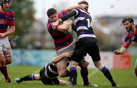 Karl Moran of Clontarf tackled by Shane Donovan and James Thornton of Terenure