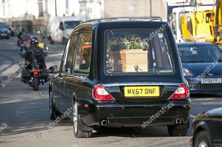 Stock Photo of The hearse carrying the coffin of the late singer Alvin Stardust makes it's way through the streets of Swansea led by a motorcycle escort from the Harley Davidson owners club.
