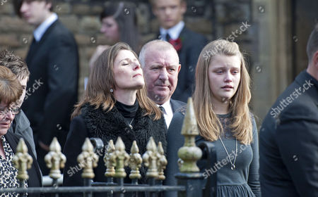 Julie Paton closes her eyes and looks skywards as she leaves the funeral of her late husband - Alvin Stardust