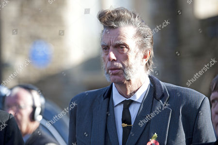 Former band member of the singer Alvin Stardust leaves his funeral in St Thomas Church in Swansea today.