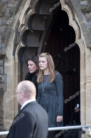 Julie Paton (left) leaves the church during the funeral of her late husband - the singer Alvin Stardust