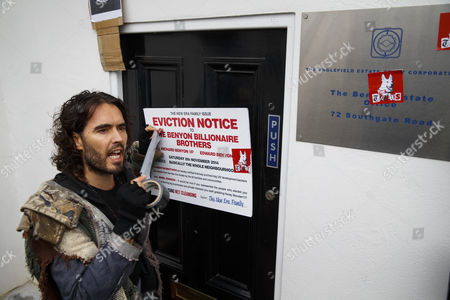 Russell Brand puts a fake eviction notice on The Benyon Estate office as he joins a group of east London residents who protest against rising housing prices and The Benyon Estate, which is owned by Conservative MP Richard Benyon and longstanding tenants of New Era Estate in Hoxton are getting their rents hiked up after the company bought the estate.