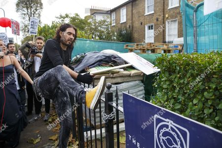 Russell Brand entering in a The Benyon Estate property to put a banner up on its scaffolding as he joins a group of east London residents who protest against rising housing prices and The Benyon Estate, which is owned by Conservative MP Richard Benyon and longstanding tenants of New Era Estate in Hoxton are getting their rents hiked up after the company bought the estate.