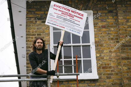 Russell Brand entering in a The Benyon Estate property to put a placard on its scaffolding as he joins a group of east London residents who protest against rising housing prices and The Benyon Estate, which is owned by Conservative MP Richard Benyon and longstanding tenants of New Era Estate in Hoxton are getting their rents hiked up after the company bought the estate.