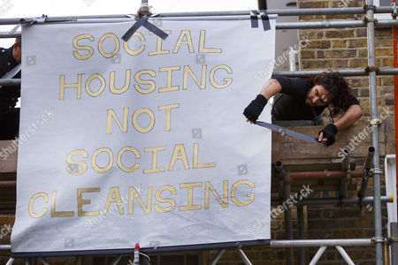 Russell Brand attaches a banner to a The Benyon Estate property's scaffolding as he joins a group of east London residents who protest against rising housing prices and The Benyon Estate, which is owned by Conservative MP Richard Benyon and longstanding tenants of New Era Estate in Hoxton are getting their rents hiked up after the company bought the estate.