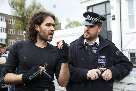 Russell Brand talking to police officers after entering in a The Benyon Estate property to put a banner up on its scaffolding as he joins a group of east London residents who protest against rising housing prices and The Benyon Estate, which is owned by Conservative MP Richard Benyon and longstanding tenants of New Era Estate in Hoxton are getting their rents hiked up after the company bought the estate.