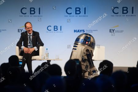 Stock Photo of John Cridland, Director-General of the CBI, looks on as Star Wars character R2D2 makes an appearance during speech of Ivan Dunleavy (not pictured), Chief Executive of Pinewood Shepperton plc