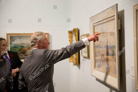 Prince Charles points at a painting detail as he talks with co-curator Sarah Milroy, left