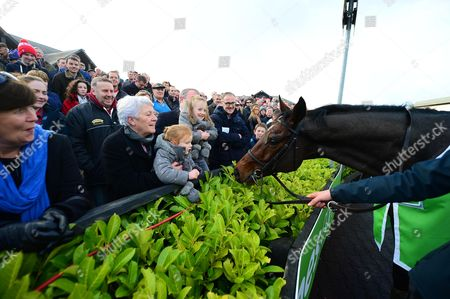 Stock Image of PUNCHESTOWN. The Stanjames.com Morgiana Hurdle. The winner HURRICANE FLY meets jockey RUBY WALSH'S children ELSA and ISABELLE with their grandmother Helen Walsh after his 20th Grade One win.