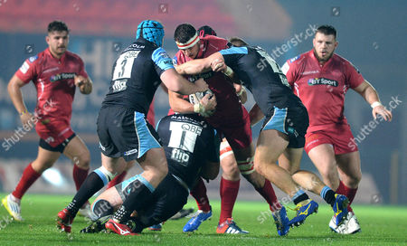 Aaron Shingler of Scarlets is tackled by Alex Allan and Ali Price of Glasgow.