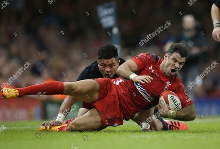 Wales' Mike Philips tackled by Keven Mealamu of New Zealand