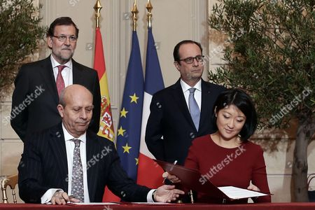 Spanish Prime Minister Mariano Rajoy and French President Francois Hollande look on while Spanish Minister of Education Jose Ignacio Wert and French Minister of Culture and Communication Fleur Pellerin sign an agreement as part of the 24th Franco-Spanish Summit
