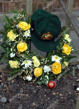 An Australian green baggie cricket cap, ball and flowers