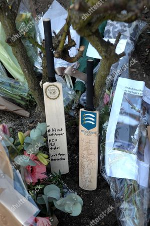 A Middlesex Country Club signed cricket bat with team members next to a Lords cricket bat with Philip Hughes' final score of '63' inscribed