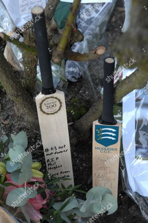 A Middlesex Country  Club signed cricket bat with team members next to a Lords cricket bat with Philip Hughes' final score of '63' inscribed left as a tribute