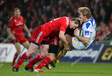 Munster's Denis Hurley and Pat Howard tackle Aurelien Rougerie of ASM Clermont Auvergne