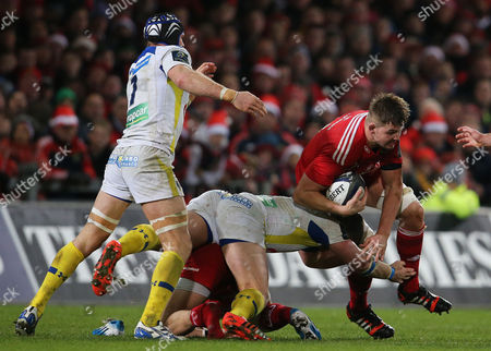 Munster's Dave Foley is tackled by Julien Bonnaire of ASM Clermont Auvergne