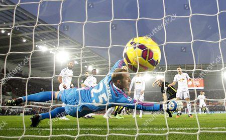 Harry Kane of Tottenham Hotspur scores a goal past Swansea City goalkeeper Gerhard Tremmel to make the score 0-1