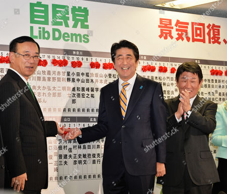 Prime Minister Shinzo Abe (C) and Sadakazu Tanigaki, Secretary-General of the Liberal Democratic Party (L) put up roses on victorious candidates' names