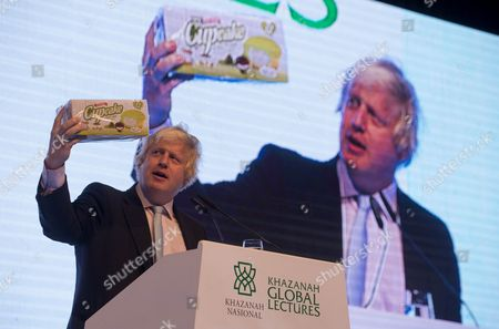 The cupcakes are his presents to the Prime Minister and The Sultan of Perak Raja Nazrin Shah to end his 6 day tour of the Far East. London Mayor Boris Johnson holds up cupcakes made in KL at the Kazanah Global Lectures in the centre of Kuala Lumpur on day 6 of his tour of the Far East. Kuala Lumpur, Malaysia