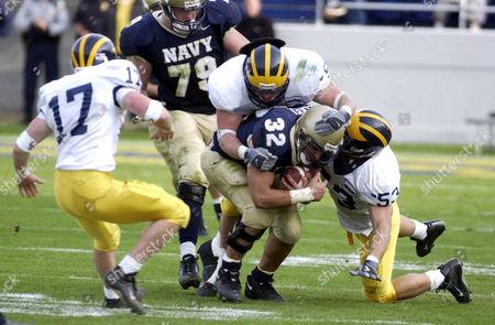 Navy junior fullback Kyle Eckel is tackled by Delaware junior linebackers Mark Moore and Ryan McDermond