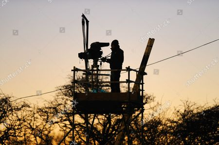 A TV cameraman set against the setting sun