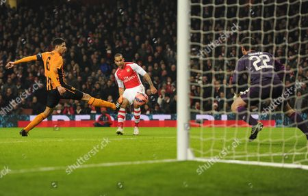 Curtis Davie tries to block the shot of Theo Walcott of Arsenal, which is saved by Hull City Goalkeeper Steve Harper